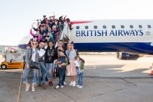 The Disney group pose with celebrities on board the aircraft steps at London City Airport